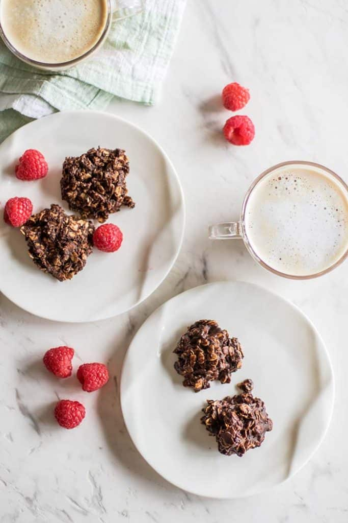Two plates with sugar free chocolate cookies, with raspberries and cups with lattes.