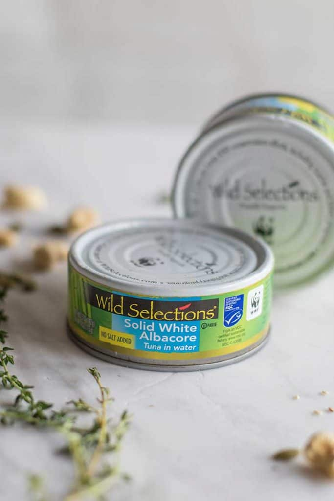 Wild Selections Tuna in a can shown with thyme sprigs and cashews.