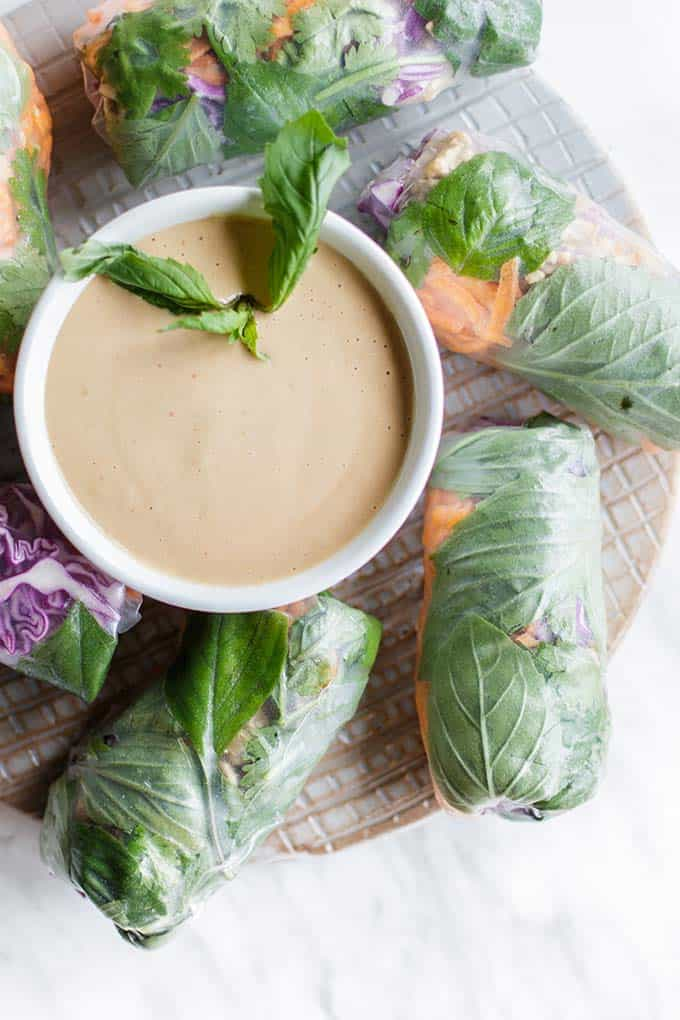 A plate with Thai spring rolls arranged around a bowl of peanut sauce.