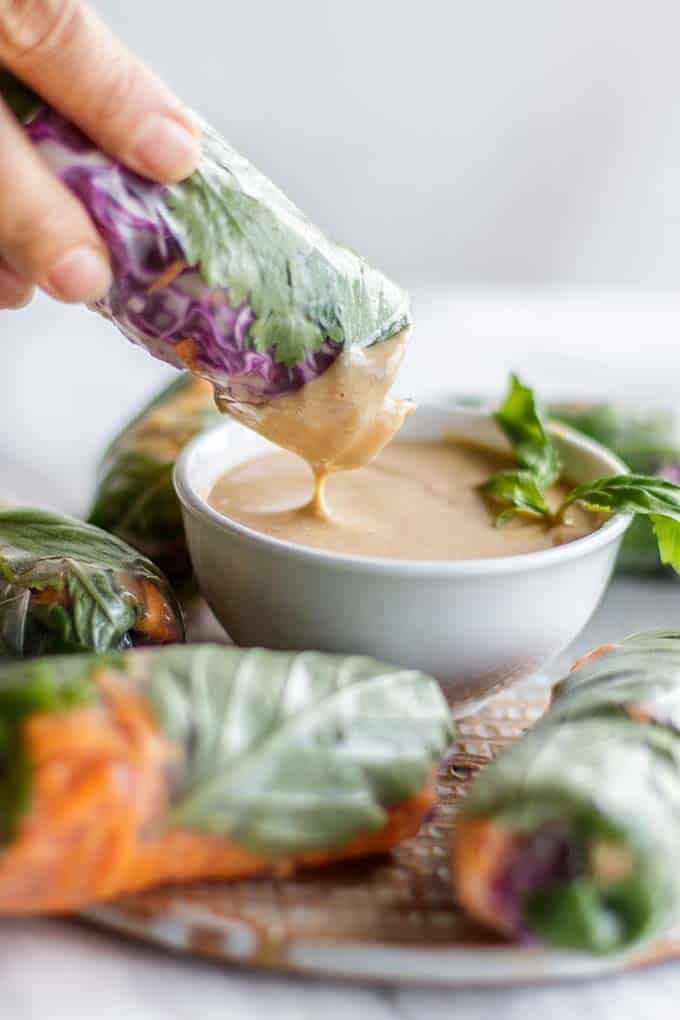 A spring roll being dipped into a creamy almond butter sauce.