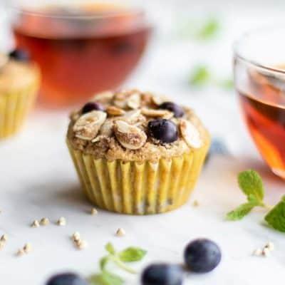 Two buckwheat muffins sitting next to mugs of tea.