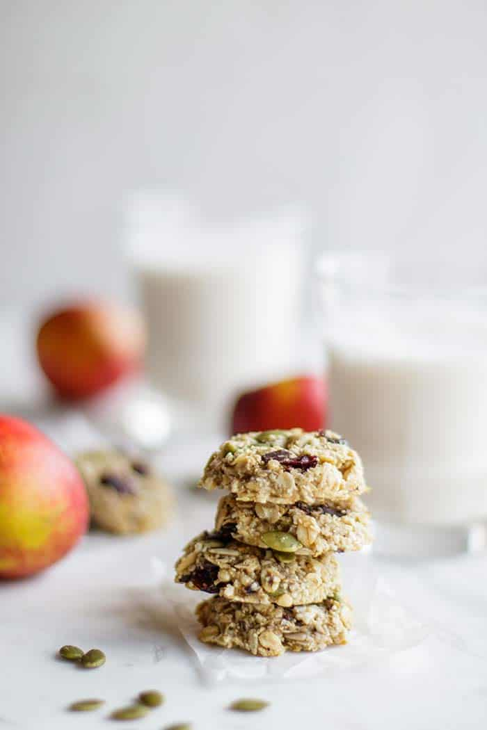 A stack of 4 banana breakfast cookies in front of a glass of milk.