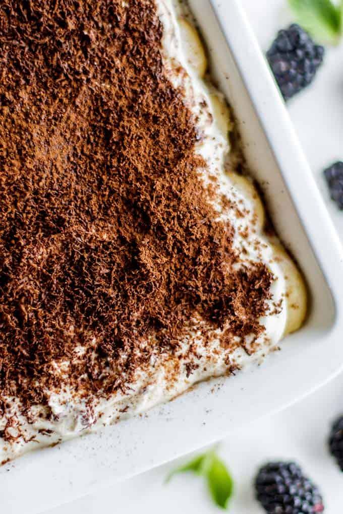 A photo of the top of the greek yogurt tiramisu, sprinkled with shaved chocolate, cinnamon, and cocoa powder.