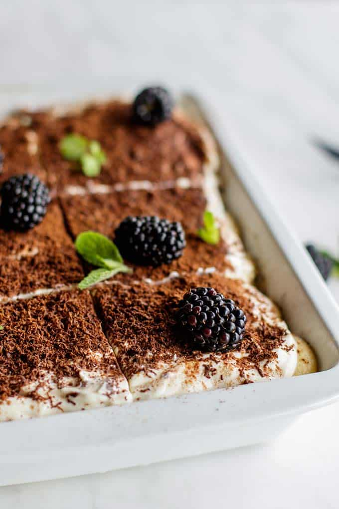 A pan of greek yogurt tiramisu shown topped with blackberries and mint.