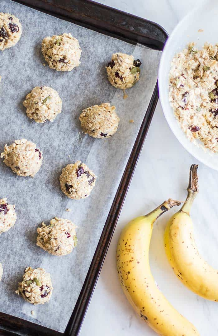 A cookie sheet with healthy gluten free breakfast cookies scooped with a tablespoon.