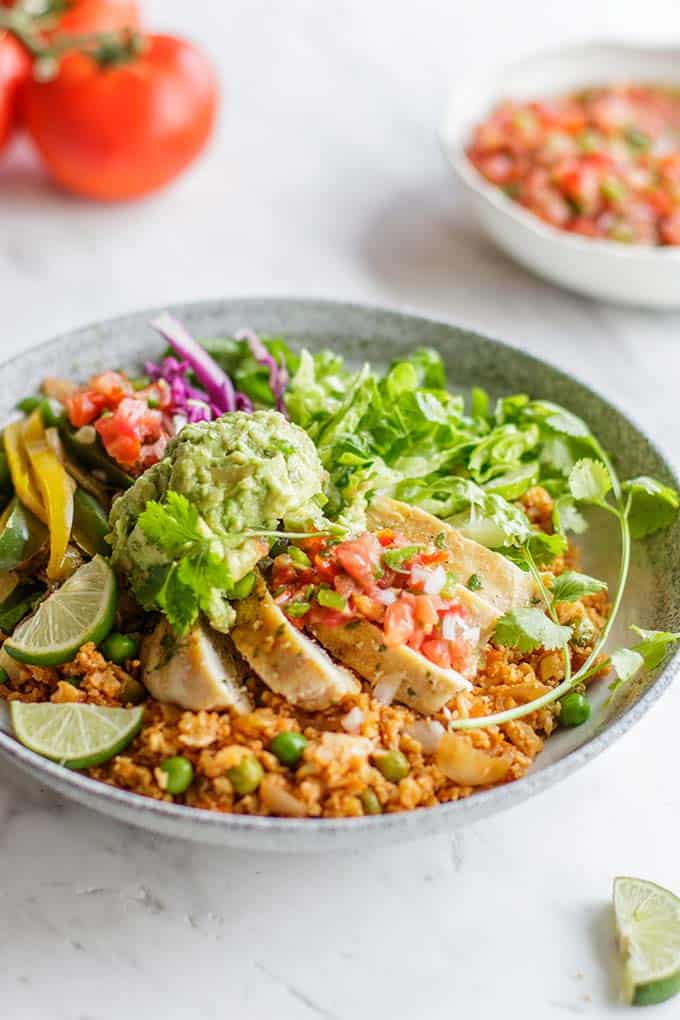 A side view of a Whole30 Chipotle Burrito Bowl, topped with chicken, salsa and guacamole.