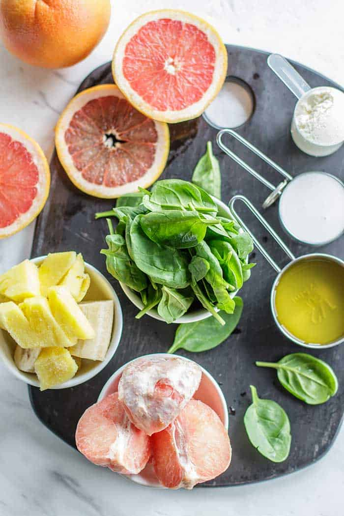 An overhead view of bowls of frozen pineapple and grapefruit, green tea, coconut milk, protein powder, and spinach.