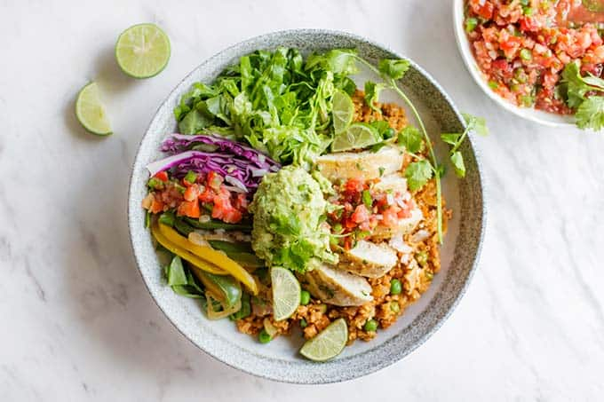 A whole30 chipotle bowl recipe showing chicken, cauliflower rice, lettuce and salsa.
