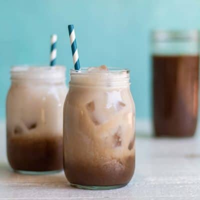 Two mason jars filled with salted caramel mocha, sitting in front of a jar of coffee concentrate.