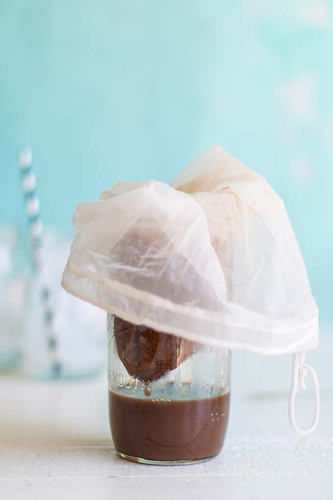 a nut milk bag straining the sediment from the coffee concentrate.