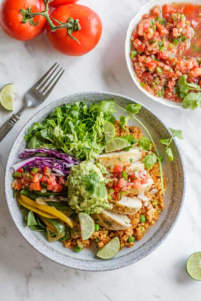 A bowl filled with cauliflower rice, lettuce, sauteed peppers and onions, chicken, and guacamole.