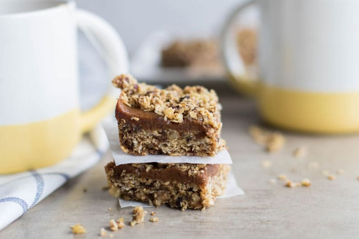 An image showing two healthy date squares stacked between two mugs of tea.