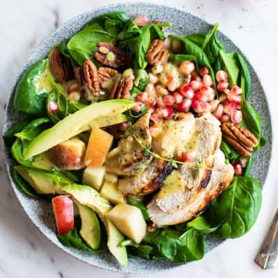 A vibrant green spinach salad topped with chicken, apples, pomegranate, pecans and avocado.