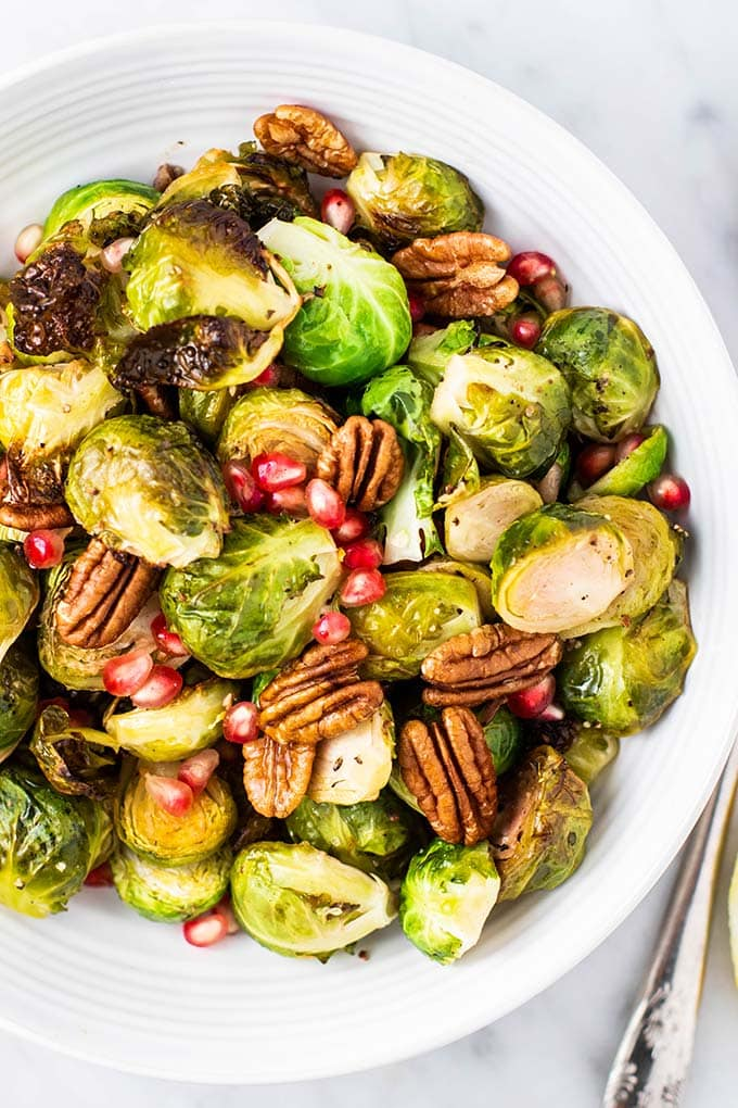 A close up of a serving bowl filled with crispy roasted brussels sprouts.