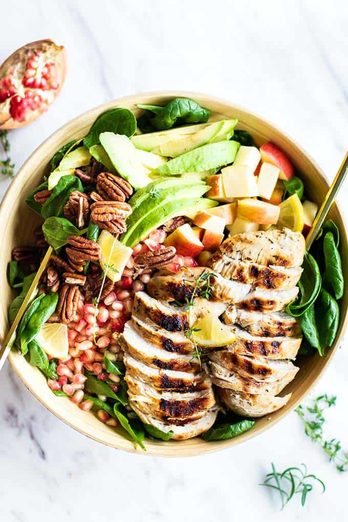 A large bowl filled with chicken spinach salad topped with herb marinated chicken.