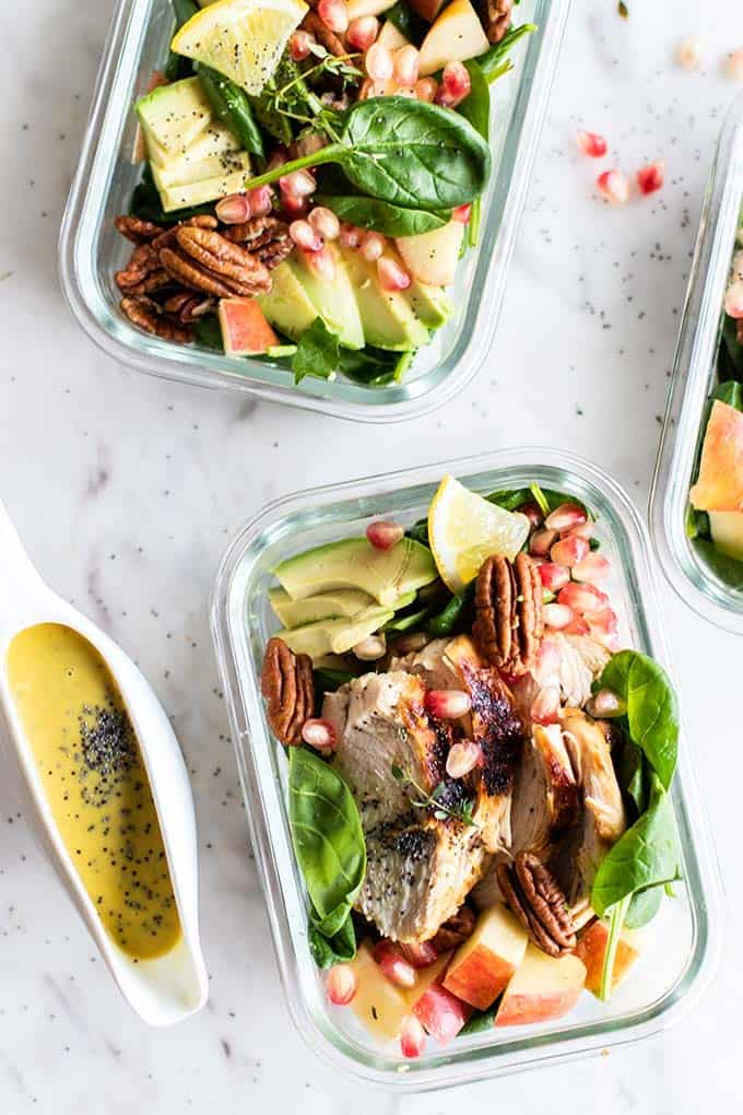 Meal prep containers filled with chicken spinach salad topped with apples and pomegranate.