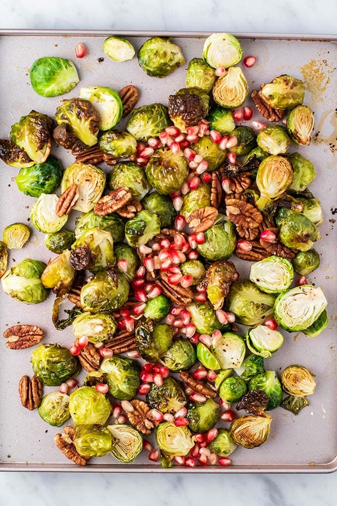 A baking sheet covered in crispy roasted brussels sprouts, topped with pecans and pomegranate.