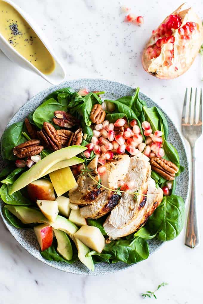 A chicken spinach salad topped with pomgranate, pecans and avocado.