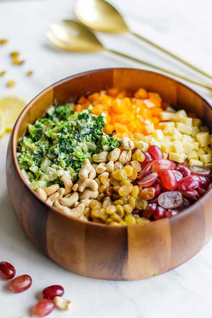 A side view of a healthy no mayo broccoli salad, in a wooden bowl with gold salad tongs.