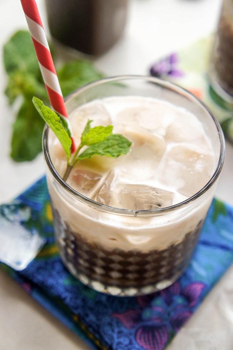 A glass with a coconut mint iced mocha, garnished with a sprig of fresh mint.