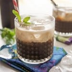 A glass filled with coffee concentrate, floated with creamy coconut milk.