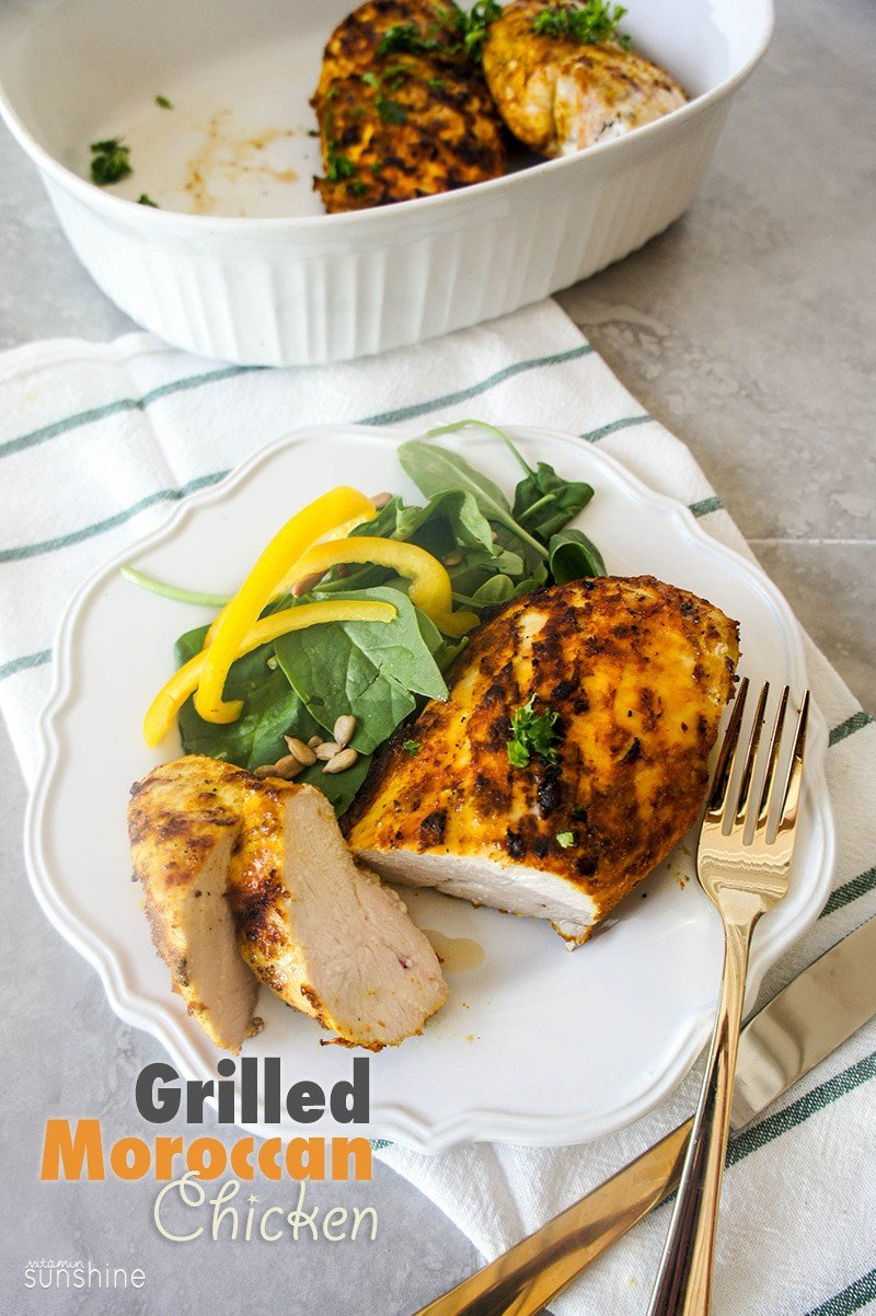 A plate with a piece of grilled Moroccan Chicken served on a simple spinach salad.