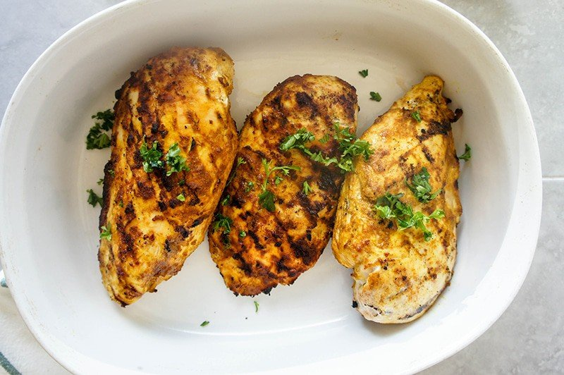3 pieces of grilled moroccan chicken in a serving dish.
