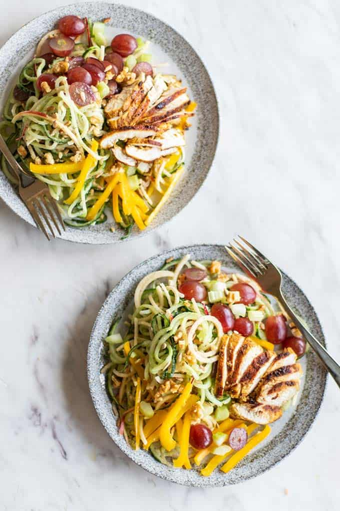Two plates of a spiralized cucumber waldorf salad.