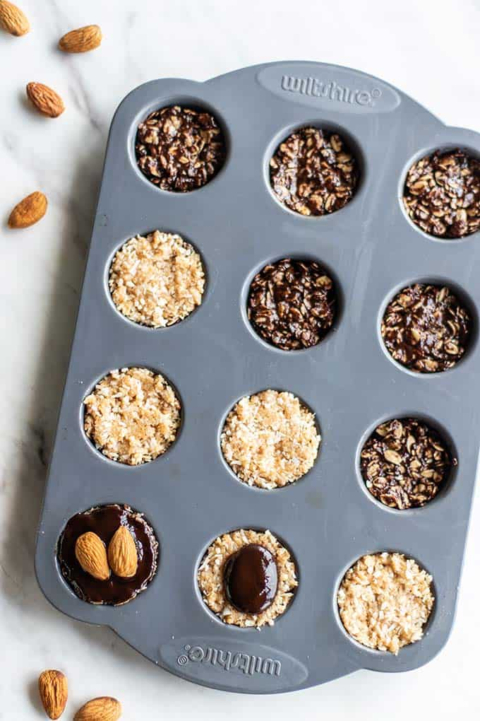 A mini muffin pan, showing how to layer the chocolate and coconut mixtures to make gluten free no bake cookies.