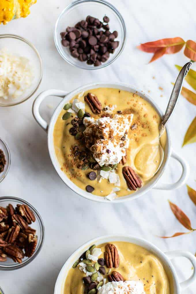 A white bowl with a pumpkin spice latte smoothie bowl with lots of topping options.