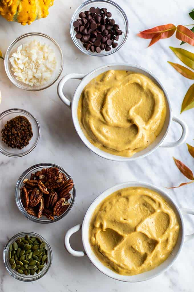 Two bowls filled with pumpkin smoothie surrounded by topping options.