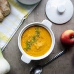 A bowl of carrot apple fennel soup with additional ingredients.