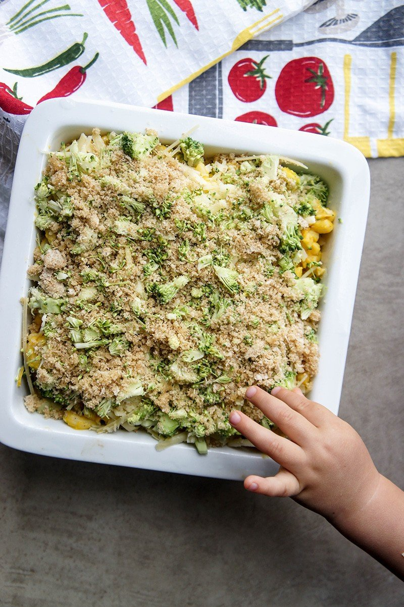 A casserole dish with an unbaked mac and cheese casserole, with a kid's hand reaching in to steal a bite.
