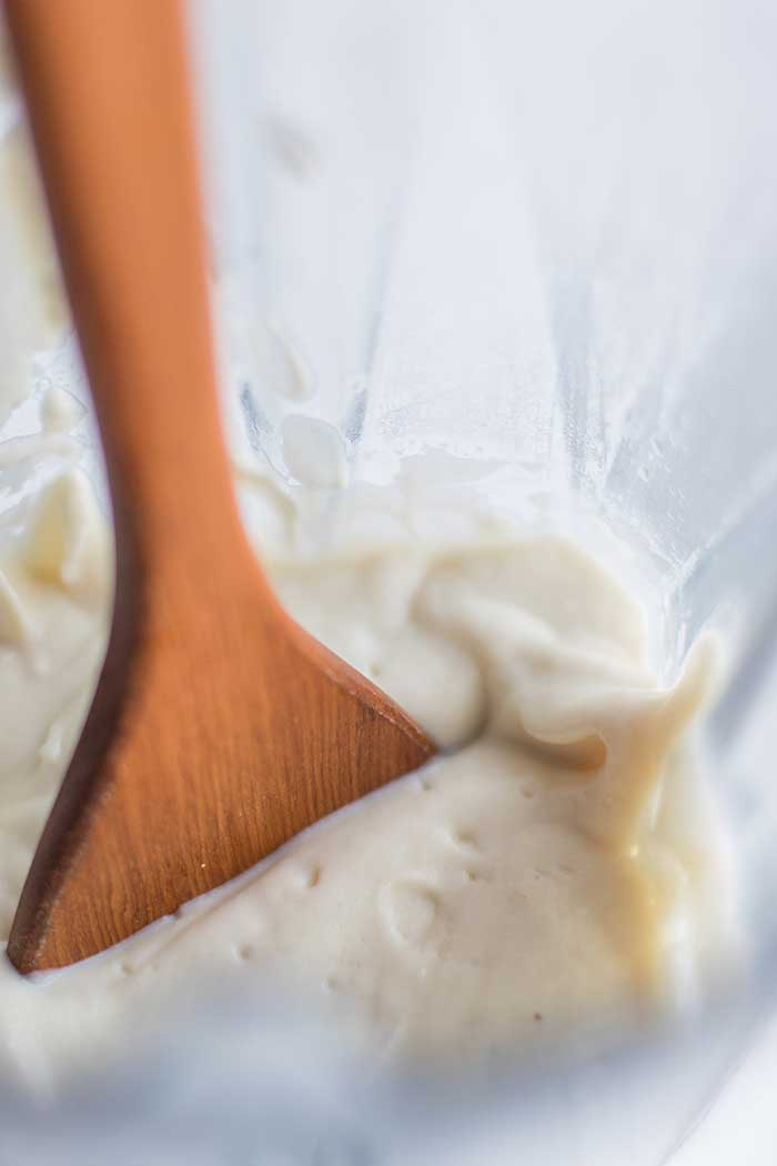 A wooden spoon dipping into a blender filled with a luxurious cashew cauliflower cream.