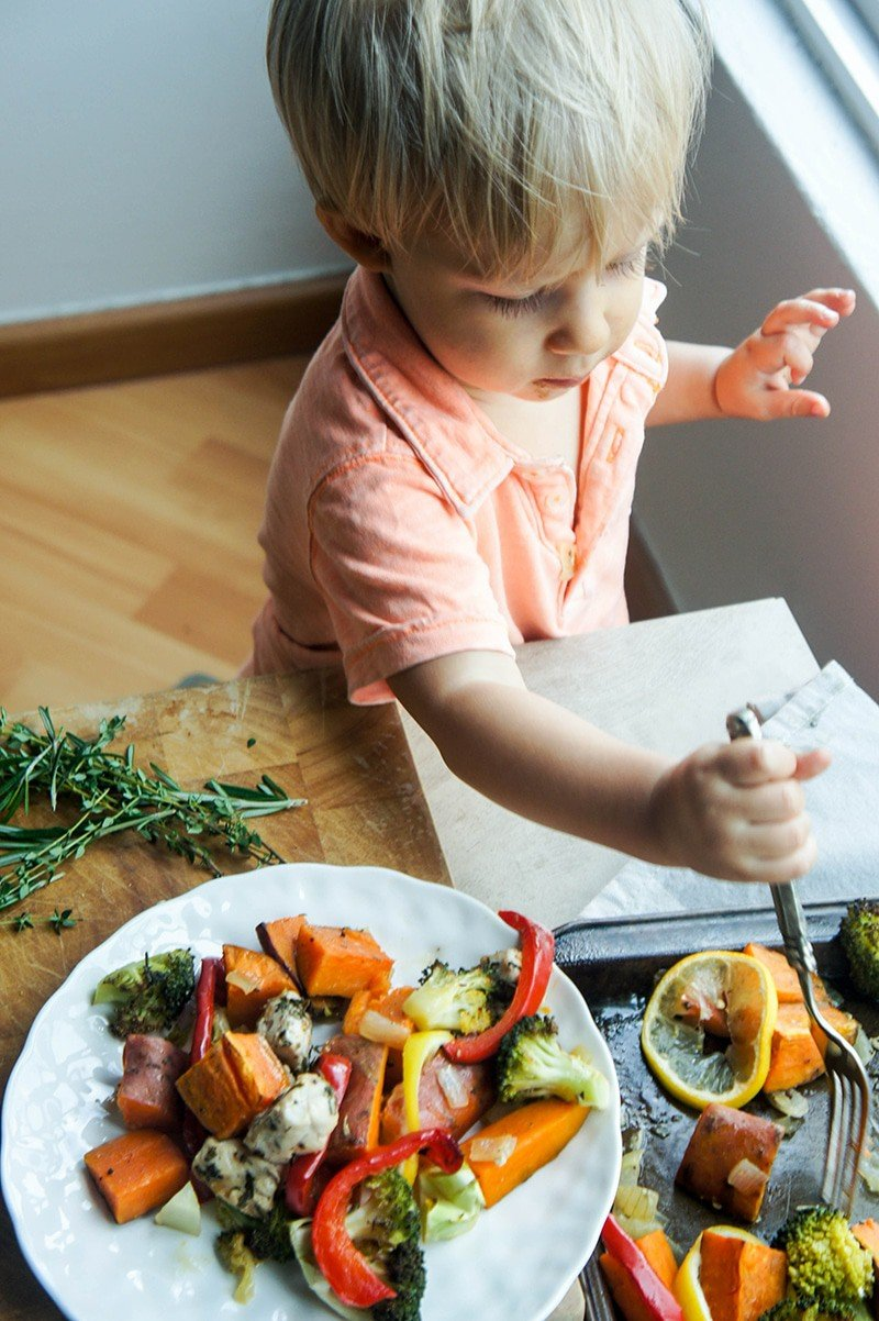 A small boy spearing a piece of broccoli off of a sheet pan.