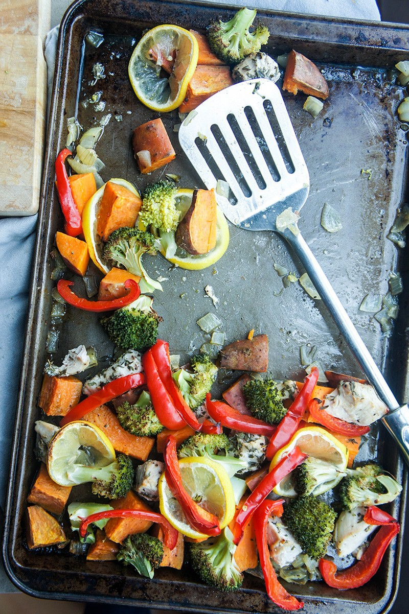 A baking tray with sweet potato, chicken, red peppers, and broccoli, baked with lemons.