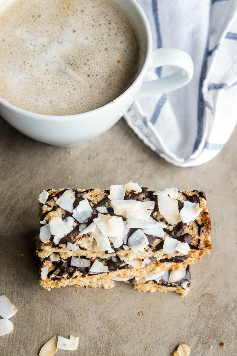 Three toasted coconut protein bars stacked in front of a mug of coffee.