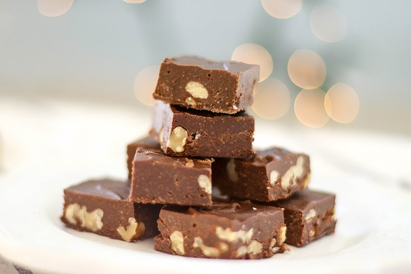 A stack of paleo fudge with walnuts on a white plate.