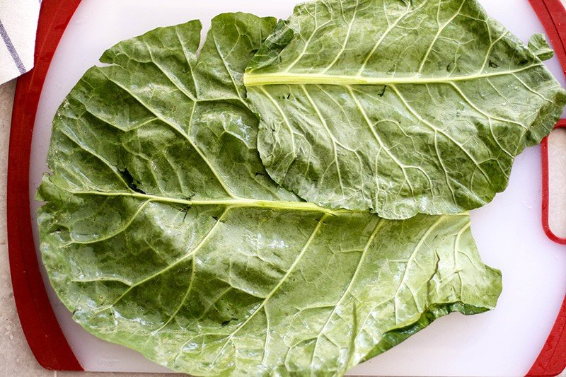 Two collard greens laying on a cutting board with the tops facing opposite directions.