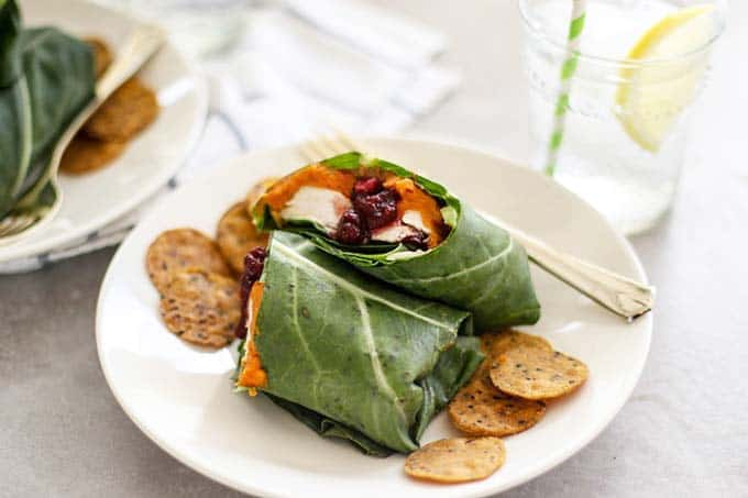 A white plate showing a collard wrap served with chips.