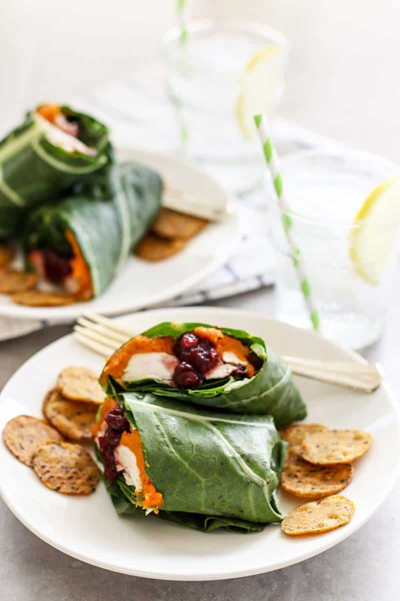 Two plates showing collard greens filled with sweet potato, turkey and cranberries.