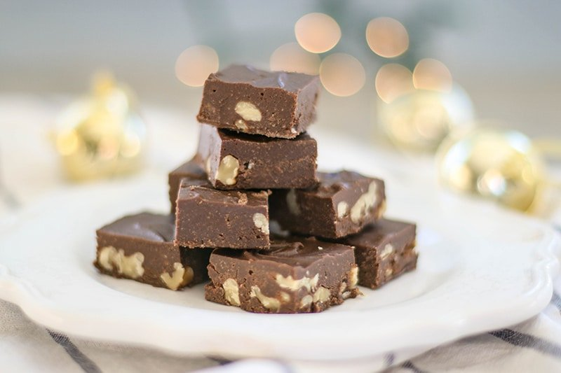 A plate with a stack of paleo fudge in front of Christmas decorations.