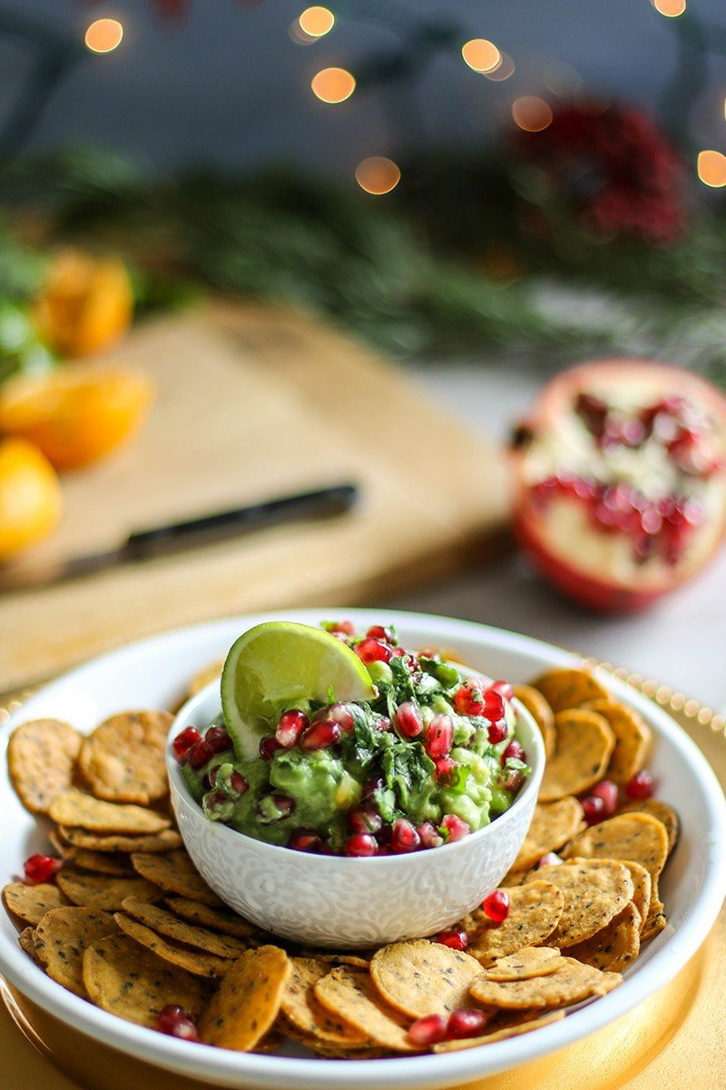 A white bowl full of pomegranate guacamole surrounded by chips.