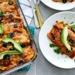 A pan of baked enchiladas topped with avocado.