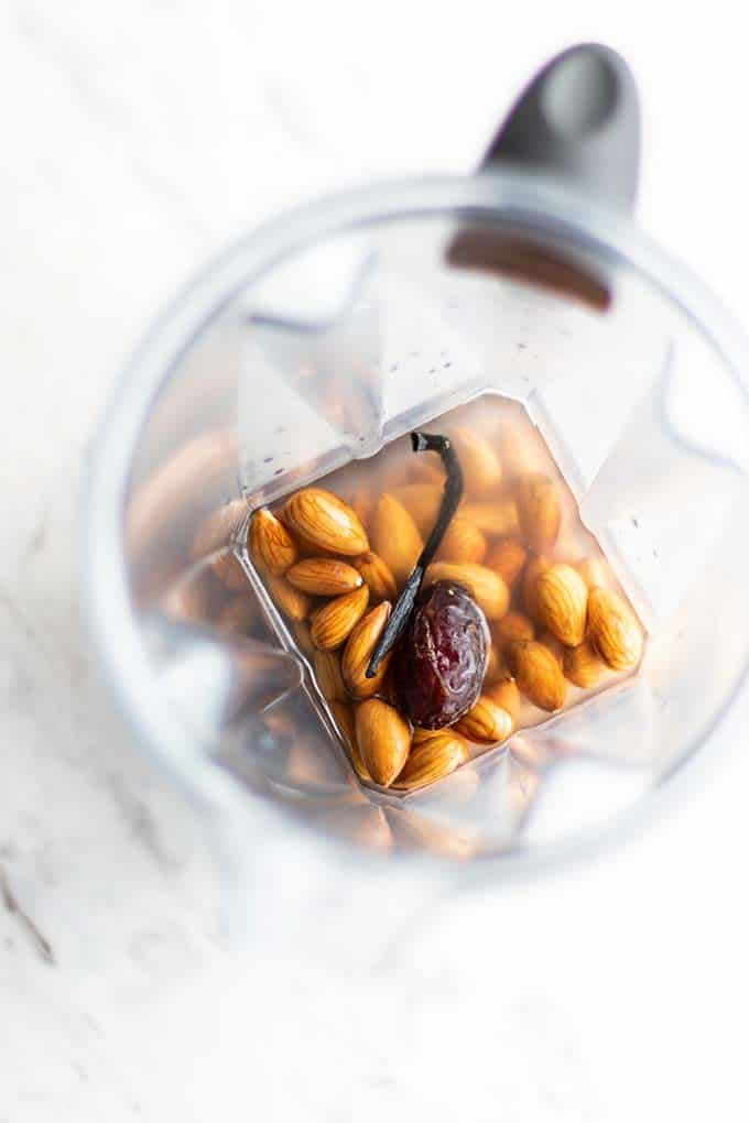 A view down into a blender with water, almonds, a date and a vanilla bean.