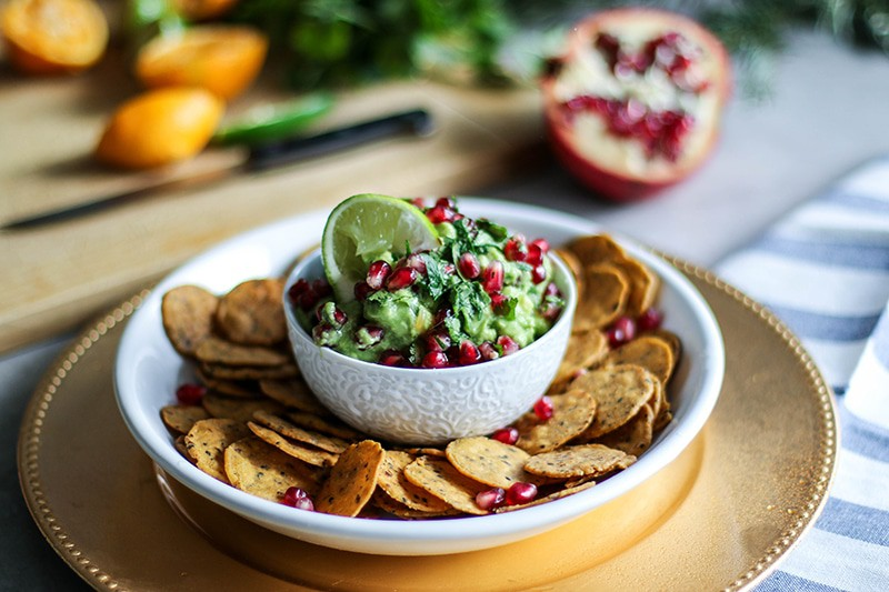 A white bowl filled with pomegranate guacamole surrounded by chips.