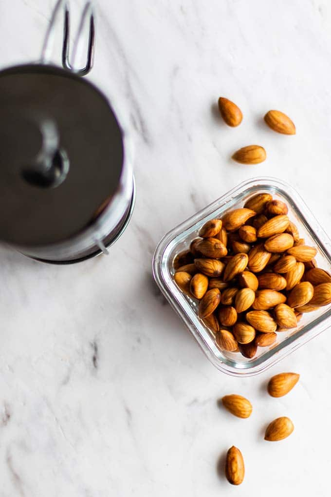 A container with plump soaked almonds, ready to be turned into almond creamer.