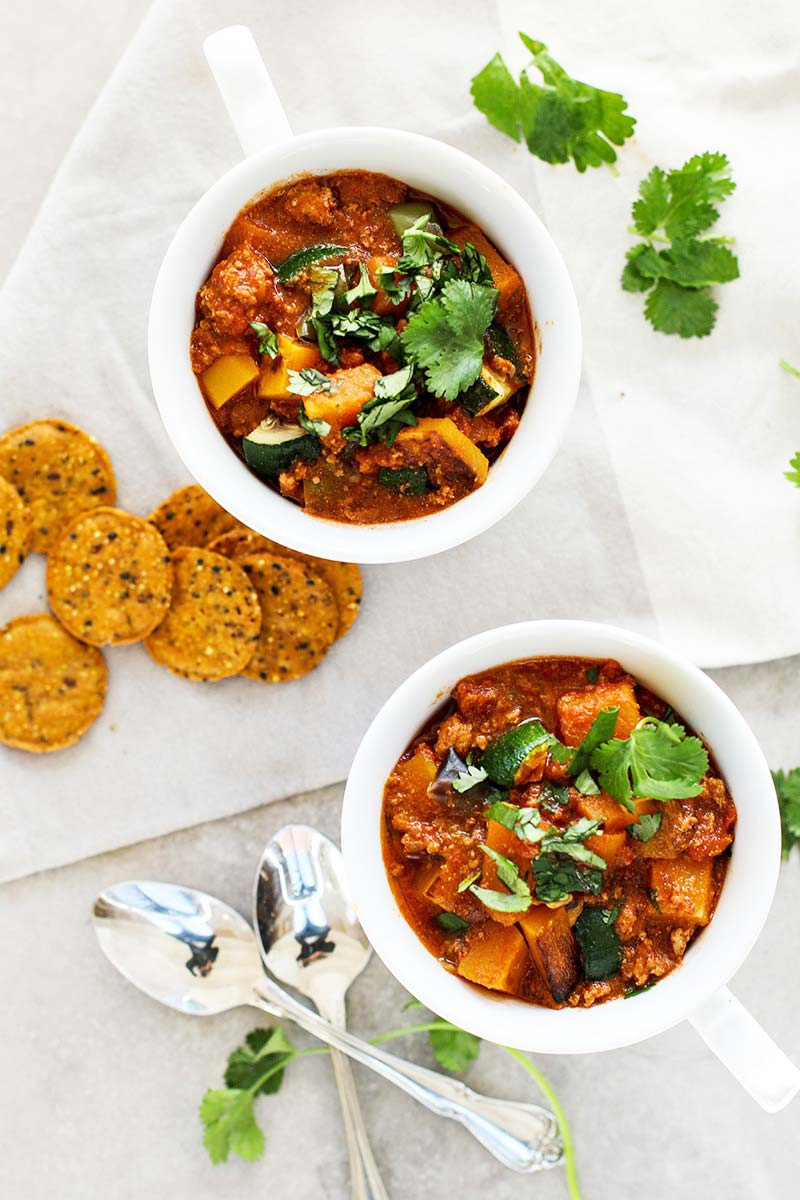 A top down view of two mugs of butternut turkey chili.