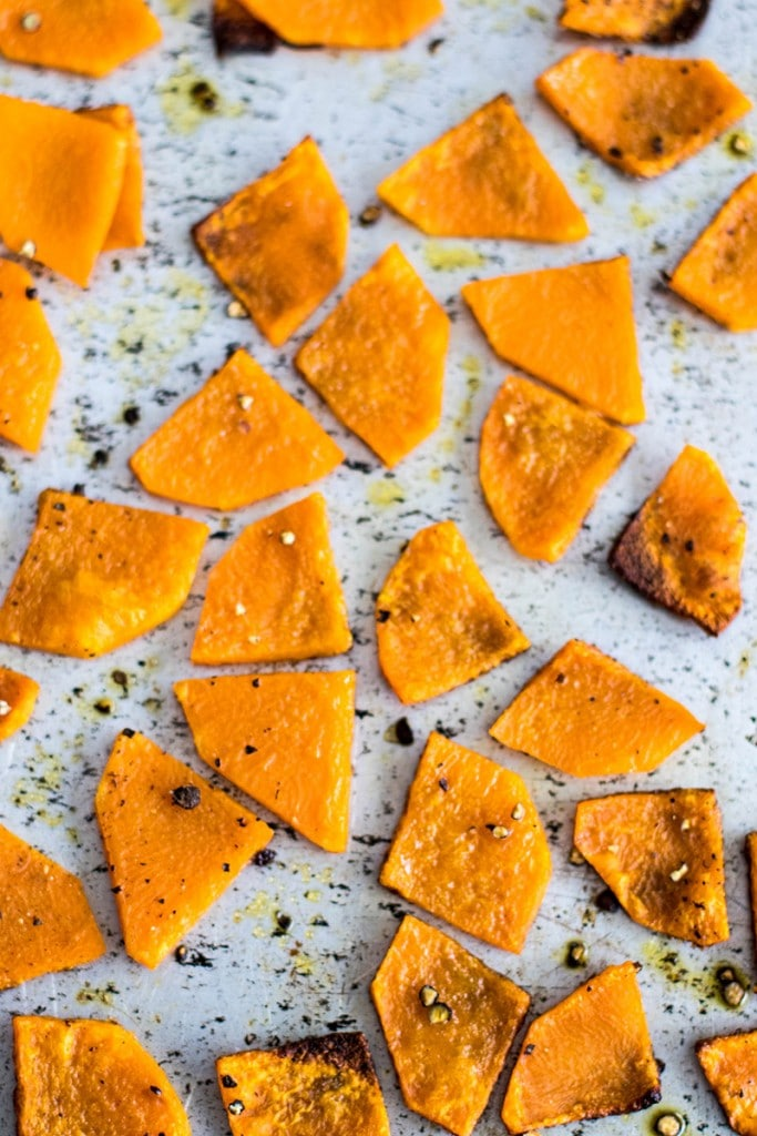 Triangles of butternut squash on a roasting pan with browned edges.