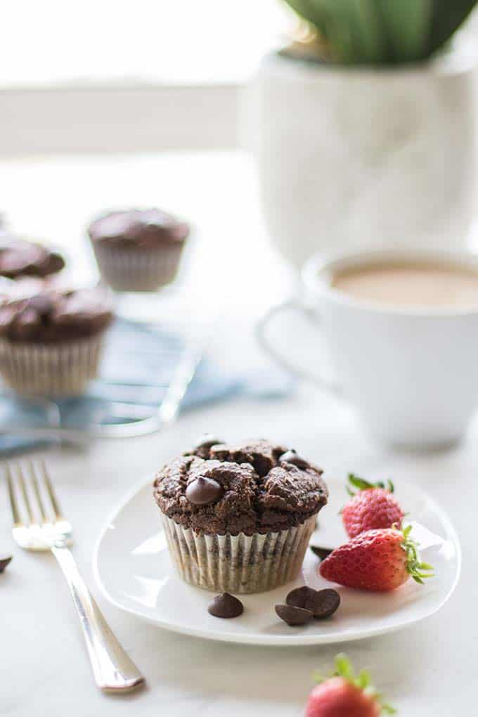 A plate with a double chocolate chip muffin and strawberries, on a table by a window.